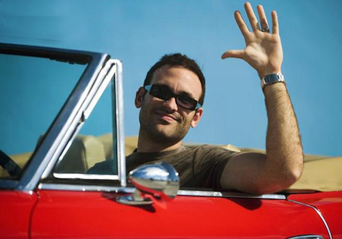 close-up_of_a_mid_adult_man_sitting_in_a_convertible_car_waving_his_hand_miami_florida_usa_gwj82773437